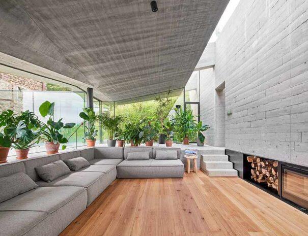 Casa rural moderna con chimenea y barbacoa en amplio salón de hormigón y madera.